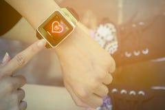Θηλυκή συμπίεση χεριών το κουμπί στο έξυπνο ρολόι Στοκ Φωτογραφίες