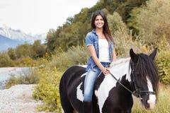 Θηλυκή συνεδρίαση αναβατών στο άλογό της και χαμόγελο Στοκ Φωτογραφία