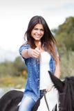 Θηλυκή συνεδρίαση αναβατών στο άλογό της στην εντάξει χειρονομία Στοκ εικόνες με δικαίωμα ελεύθερης χρήσης