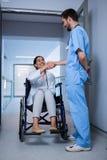 Θηλυκή συνεδρίαση γιατρών σε ετοιμότητα την αναπηρική καρέκλα και τινάγματος με νοσοκόμος Στοκ εικόνα με δικαίωμα ελεύθερης χρήσης