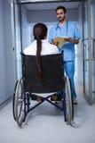 Θηλυκή συνεδρίαση γιατρών στην αναπηρική καρέκλα και αλληλεπίδραση με νοσοκόμος Στοκ Εικόνες