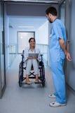 Θηλυκή συνεδρίαση γιατρών στην αναπηρική καρέκλα και αλληλεπίδραση με νοσοκόμος Στοκ Φωτογραφία