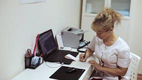Θηλυκή συνεδρίαση γιατρών στον πίνακα και γράψιμο στα αποτελέσματα ηλεκτροκαρδιογραφημάτων απόθεμα βίντεο