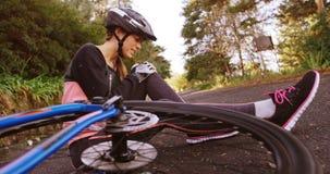 Θηλυκή συνεδρίαση ποδηλατών βουνών στο έδαφος στον πόνο φιλμ μικρού μήκους