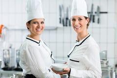 Θηλυκοί αρχιμάγειρες στην εμπορική κουζίνα που φορά τις άσπρες στολές Στοκ εικόνα με δικαίωμα ελεύθερης χρήσης