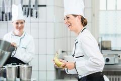 Θηλυκοί αρχιμάγειρες στην εμπορική κουζίνα που φορά τις άσπρες στολές Στοκ Εικόνα