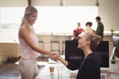 Θηλυκοί επιχειρηματίες που τινάζουν τα χέρια στο δημιουργικό γραφείο Στοκ φωτογραφία με δικαίωμα ελεύθερης χρήσης