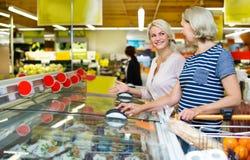Θηλυκοί πελάτες κοντά στην επίδειξη με τα παγωμένα τρόφιμα Στοκ Φωτογραφίες