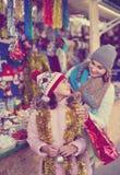 Θηλυκοί πελάτες που κοιτάζουν επίμονα στο μετρητή της αγοράς Χριστουγέννων Στοκ Φωτογραφία