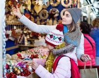 Θηλυκοί πελάτες που κοιτάζουν επίμονα στο μετρητή της αγοράς Χριστουγέννων Στοκ Εικόνα