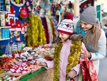 Θηλυκοί πελάτες που κοιτάζουν επίμονα στο μετρητή της αγοράς Χριστουγέννων Στοκ Εικόνες
