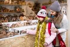 Θηλυκοί πελάτες που κοιτάζουν επίμονα στο μετρητή του περίπτερου με τους αριθμούς για το χρώμιο Στοκ εικόνες με δικαίωμα ελεύθερης χρήσης