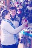 Θηλυκοί συνταξιούχοι που αγοράζουν τις διακοσμήσεις Χριστουγέννων στην έκθεση Στοκ Φωτογραφία