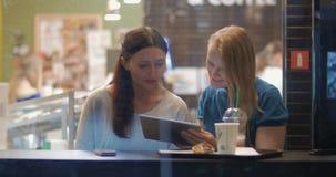 Θηλυκοί φίλοι που μιλούν και που χρησιμοποιούν το μαξιλάρι αφής στον καφέ απόθεμα βίντεο