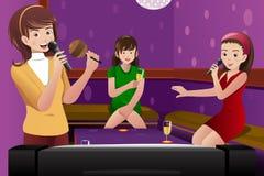 Θηλυκοί φίλοι που τραγουδούν το καραόκε Στοκ Φωτογραφία