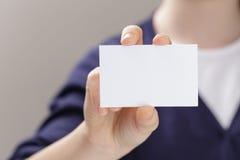 Θηλυκός έφηβος που κρατά την κενή επαγγελματική κάρτα μπροστά από τη κάμερα Στοκ Φωτογραφία