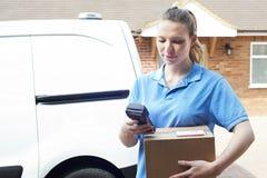 Θηλυκός αγγελιαφόρος που παραδίδει τη συσκευασία στο εσωτερικό σπίτι στοκ φωτογραφίες με δικαίωμα ελεύθερης χρήσης