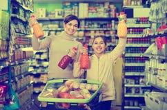 Θηλυκός αγοραστής με το έφηβη κόρη που ψάχνει για τα ποτά Στοκ Εικόνα