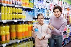 Θηλυκός αγοραστής με το έφηβη κόρη που ψάχνει για τα ποτά Στοκ φωτογραφία με δικαίωμα ελεύθερης χρήσης