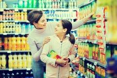 Θηλυκός αγοραστής με το έφηβη κόρη που ψάχνει για τα ποτά Στοκ Φωτογραφία