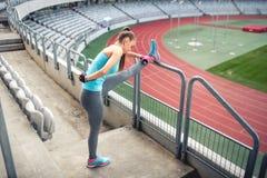 Θηλυκός αθλητής που εκπαιδεύει και που τεντώνει για το ζέσταμα στα σκαλοπάτια στοκ φωτογραφίες