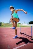 Θηλυκός αθλητής που πηδά επάνω από το εμπόδιο Στοκ εικόνα με δικαίωμα ελεύθερης χρήσης