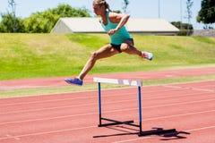 Θηλυκός αθλητής που πηδά επάνω από το εμπόδιο Στοκ Φωτογραφία