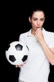 Θηλυκός αθλητής που φυσά έναν συριγμό και που κρατά μια σφαίρα ποδοσφαίρου Στοκ Εικόνες