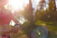 Θηλυκός αθλητής που χρησιμοποιεί την ικανότητα app στο έξυπνο ρολόι της για να ελέγξει workout την απόδοση Στοκ Φωτογραφίες