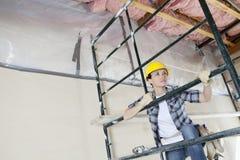Θηλυκός ανάδοχος που αναρριχείται στο ικρίωμα εξετάζοντας μακριά το εργοτάξιο οικοδομής Στοκ Εικόνες