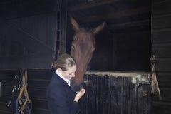 Θηλυκός αναβάτης πλατών αλόγου με το άλογο στο σταύλο Στοκ Εικόνες