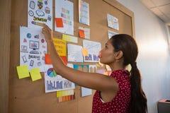 Θηλυκός ανώτερος υπάλληλος που δείχνει το έγγραφο σχετικά με τον πίνακα δελτίων Στοκ Εικόνες