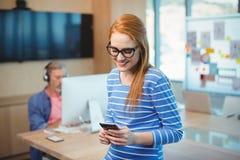 Θηλυκός ανώτερος υπάλληλος που χρησιμοποιεί το κινητό τηλέφωνο στην αρχή Στοκ εικόνες με δικαίωμα ελεύθερης χρήσης