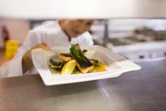 Θηλυκός αρχιμάγειρας με τα μαγειρευμένα τρόφιμα στην κουζίνα Στοκ Εικόνες