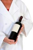 Θηλυκός αρχιμάγειρας με το μπουκάλι του κρασιού στοκ εικόνα