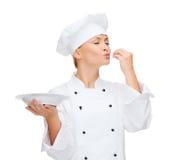 Θηλυκός αρχιμάγειρας με το πιάτο που παρουσιάζει εύγευστο σημάδι Στοκ Εικόνες