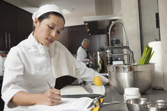 Θηλυκός αρχιμάγειρας που γράφει στην περιοχή αποκομμάτων στην κουζίνα στοκ εικόνες με δικαίωμα ελεύθερης χρήσης