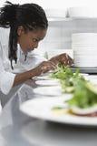 Θηλυκός αρχιμάγειρας που προετοιμάζει τη σαλάτα στην κουζίνα Στοκ Εικόνες