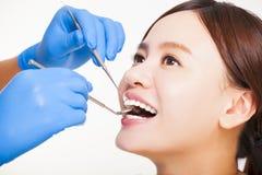 θηλυκός ασθενής που έχει τα δόντια εξετασμένων από τον οδοντίατρο Στοκ εικόνα με δικαίωμα ελεύθερης χρήσης
