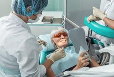 Θηλυκός ασθενής που λαμβάνει τη θεραπεία από τον οδοντίατρο Στοκ φωτογραφία με δικαίωμα ελεύθερης χρήσης