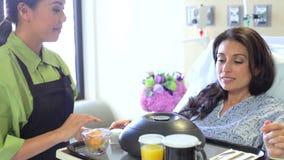 Θηλυκός ασθενής που είναι εξυπηρετούμενο γεύμα στο νοσοκομειακό κρεβάτι απόθεμα βίντεο