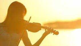 Θηλυκός βιολιστής που παίζει το βιολί στη λίμνη στο ηλιοβασίλεμα απόθεμα βίντεο