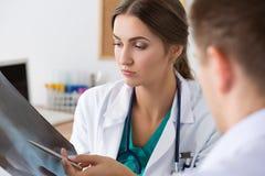 Θηλυκός γιατρός ιατρικής που παρουσιάζει κάτι στον άνδρα συνάδελφός της ο Στοκ φωτογραφία με δικαίωμα ελεύθερης χρήσης