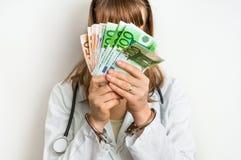 Θηλυκός γιατρός με τα χρήματα και τις χειροπέδες - έννοια δωροδοκιών Στοκ Εικόνα