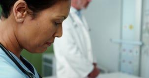 Θηλυκός γιατρός που γεμίζει τη μορφή ιατρικής ασφάλειας φιλμ μικρού μήκους