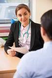 Θηλυκός γιατρός που διοργανώνει τη συζήτηση με τον αρσενικό ασθενή στη χειρουργική επέμβαση Στοκ φωτογραφία με δικαίωμα ελεύθερης χρήσης
