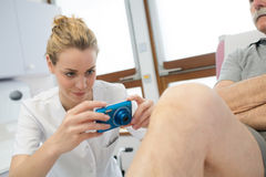 Θηλυκός γιατρός που παίρνει τραυματισμένο το εικόνα γόνατο Στοκ φωτογραφία με δικαίωμα ελεύθερης χρήσης