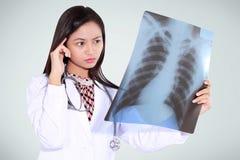 Θηλυκός γιατρός που σκέφτεται και που διαβάζει την ακτίνα X στοκ φωτογραφία