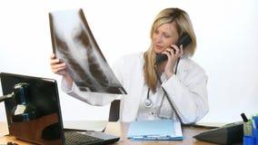 Θηλυκός γιατρός στο τηλέφωνο και τη μελέτη μιας ακτίνας X απόθεμα βίντεο