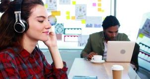 Θηλυκός γραφικός σχεδιαστής που εργάζεται ενώ μουσική ακούσματος στο γραφείο απόθεμα βίντεο